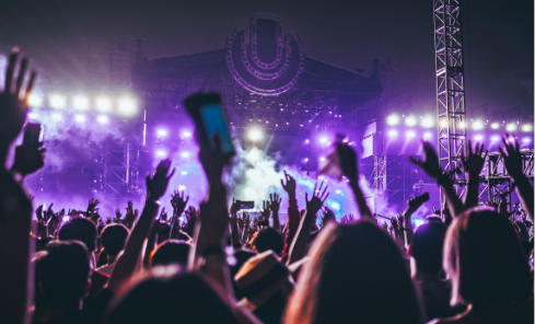 people holding their hands up at a concert