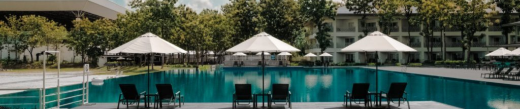 wide shot of a hotel pool area with chairs and umbrellas