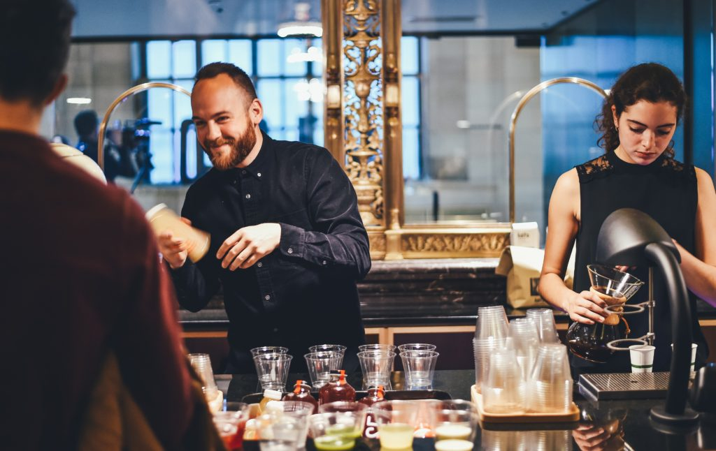male and female bartender making drinks