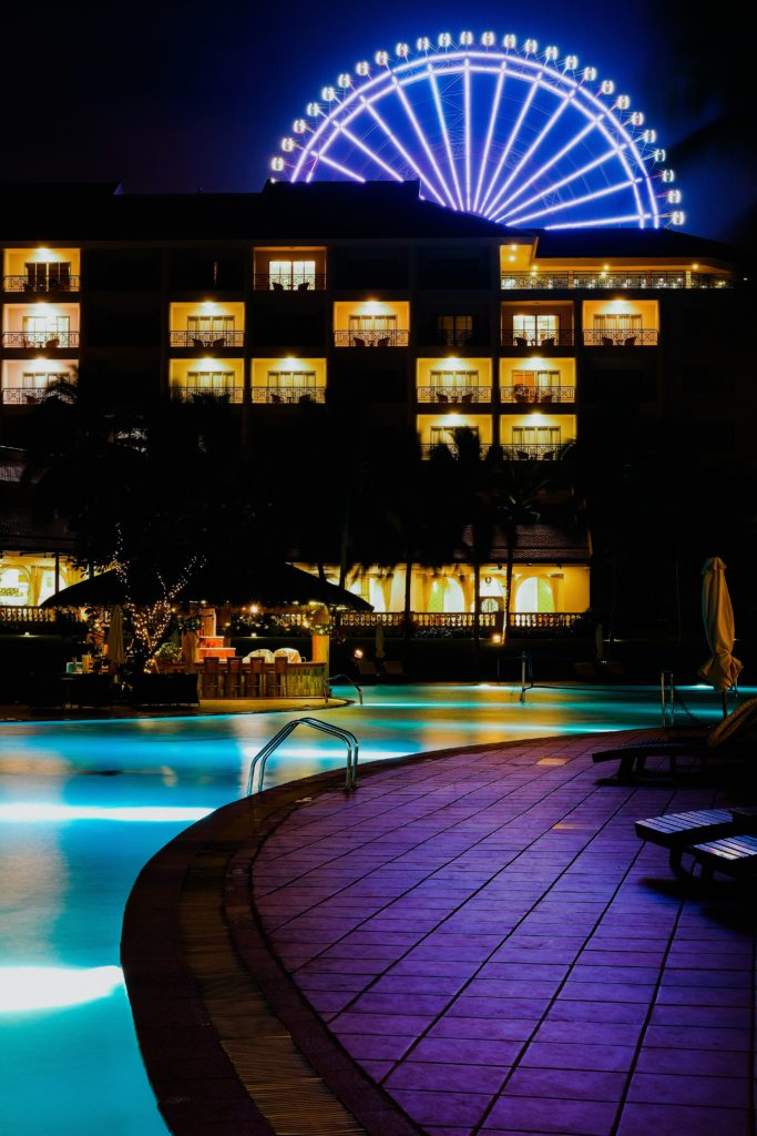 hotel pool area at night with ferris wheel in background