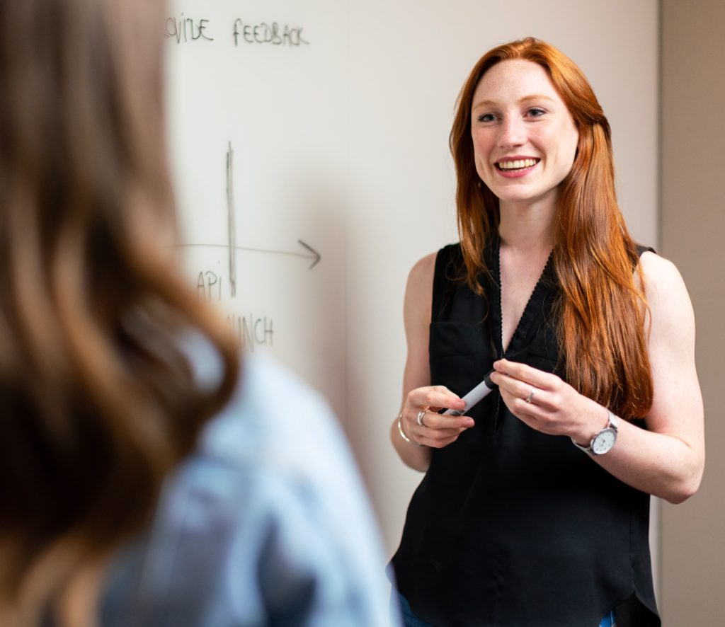 woman holding a pen next to a whiteboard talking to another person