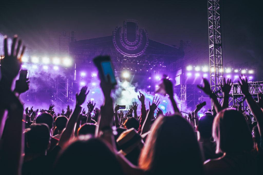 people holding up their hands at a festival