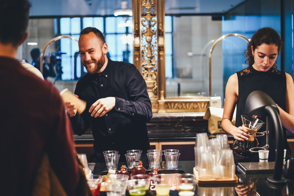 two bartenders working behind a hotel bar mixing drinks