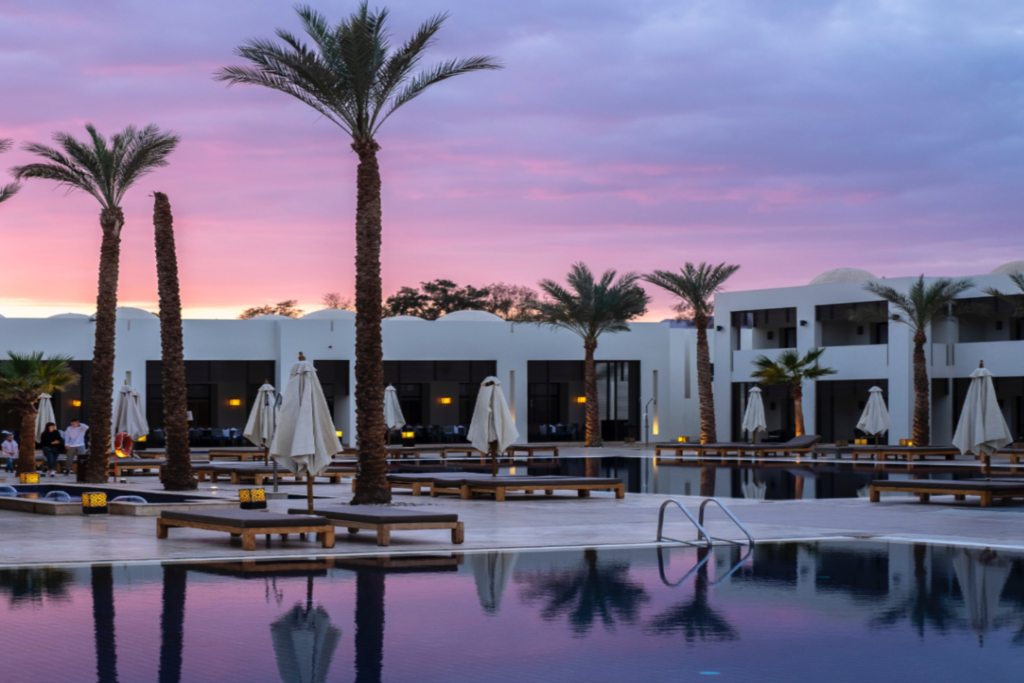 hotel apartments overlooking a swimming pool and sunbeds in dusk
